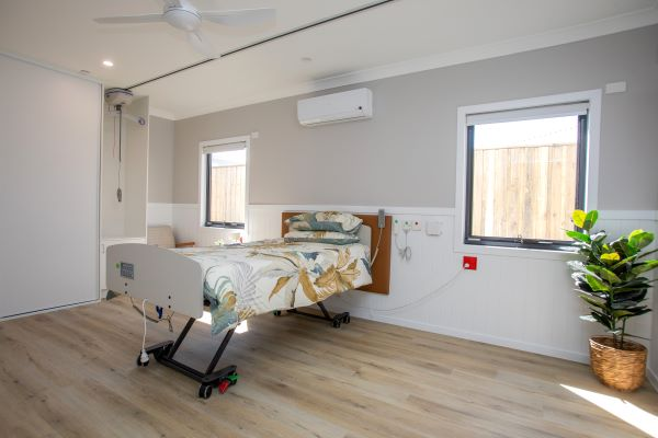 Hospital style bed in light filled room with plant in corner