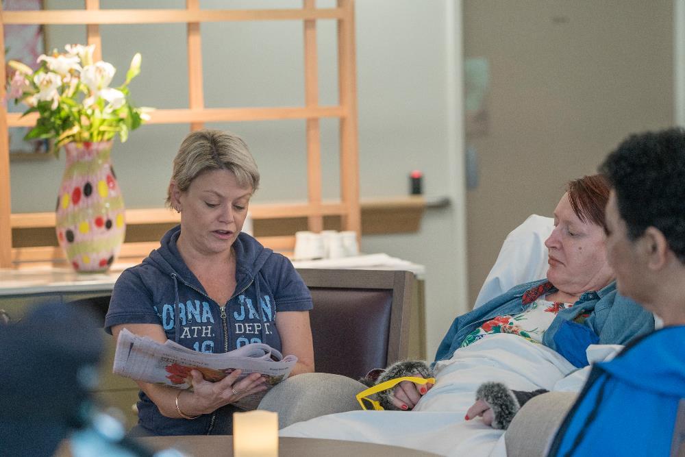 WesleyCare Jindalee staff member reading to resident