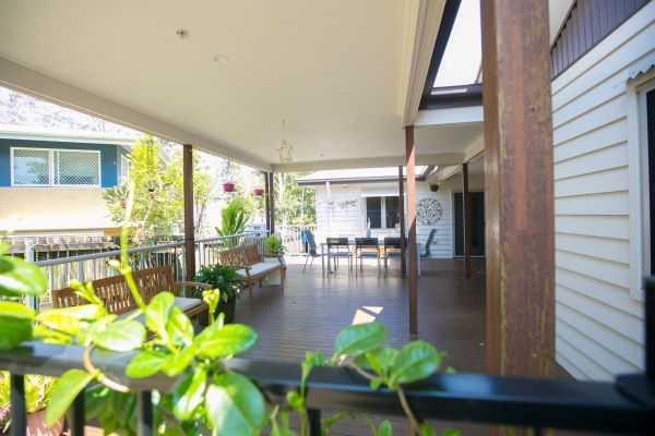 WesleyCare Tewantin deck with plants in foreground and table and chairs