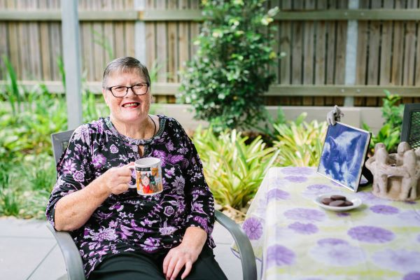 Wynnum Apartments resident sits with a cup of coffee outside