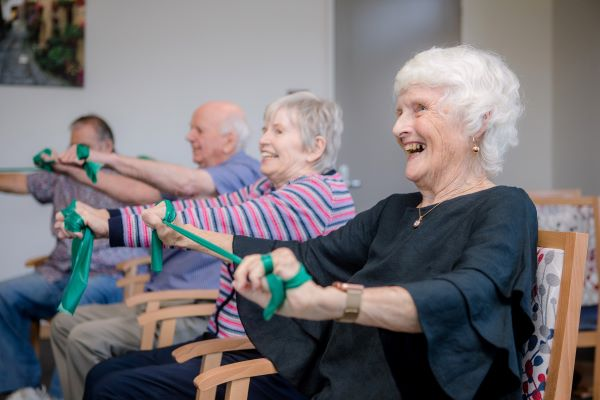 Older people smiling and exercising together in chairs with therabands