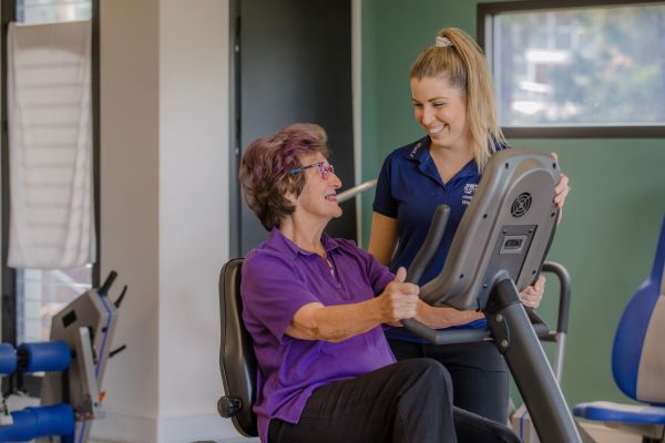 Staff member speaks to client on exercise machine