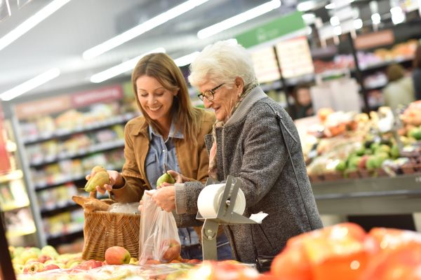 Two people selecting fruit at supermarket