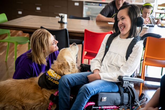 Girl in wheelchair smiling at therapy dog