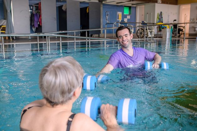 Lady working out in a hydrotherapy pool with staff member