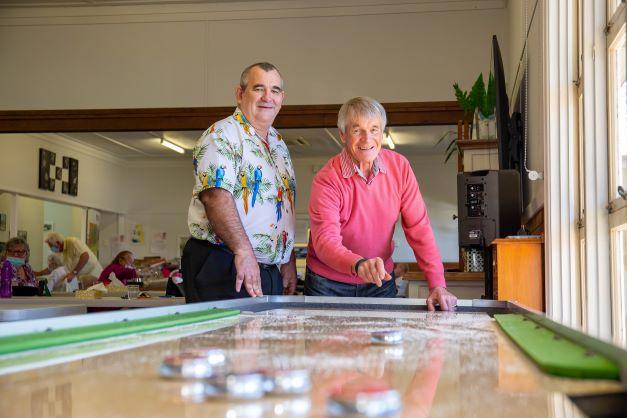 Two men enjoying a game of shuffleboard at Hyland House Respite Centre