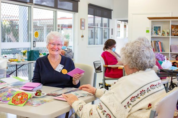 Ladies sit at table smiling with handmade cards