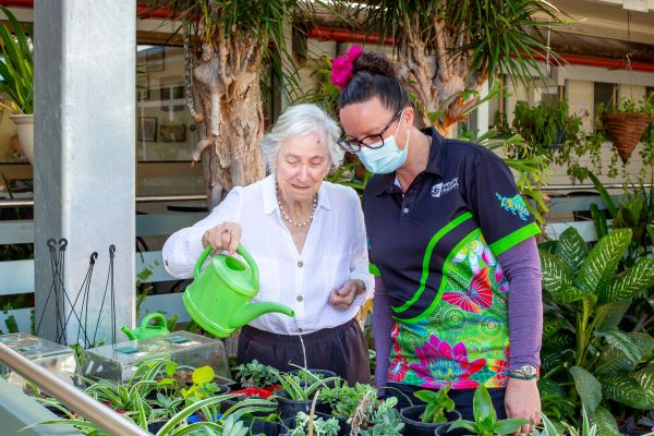 Older lady watering plants while masked staff member looks on