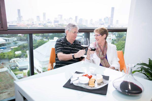 Couple enjoy drinks on balcony