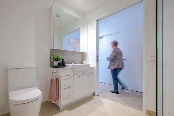 Lady walks past bathroom