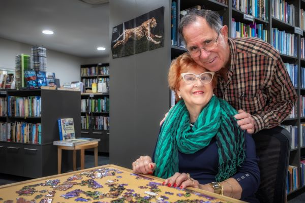 Couple complete jigsaw in library