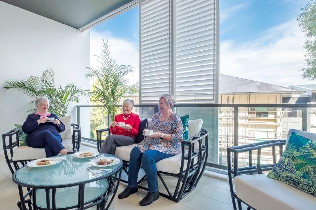 Friends on a balcony enjoying a coffee