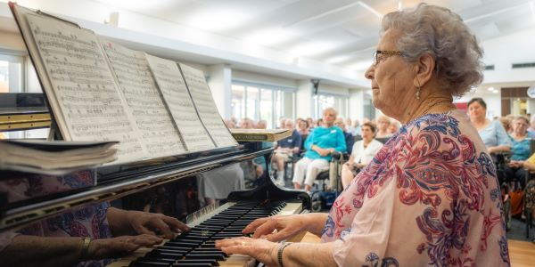 Lady sits at piano entertaining retirees