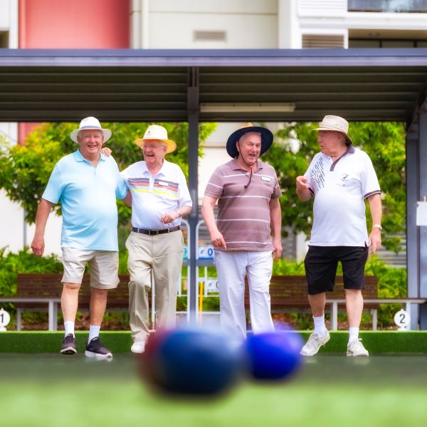 Group of men play lawn bowls