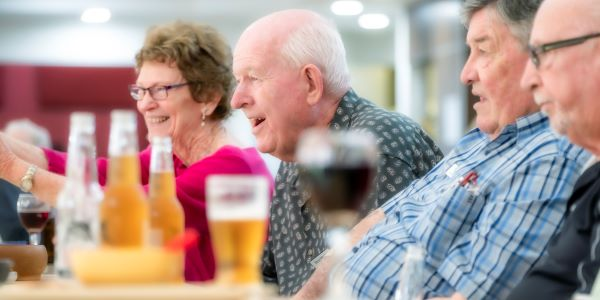 Retirees laughing over drinks