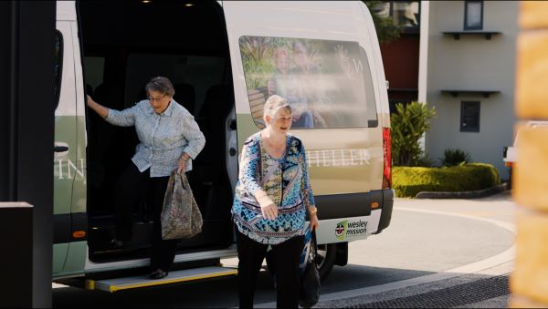 Ladies leave bus with shopping