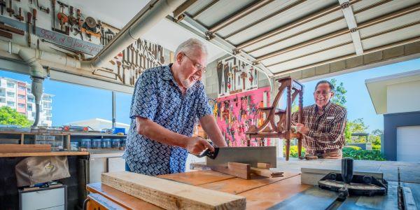 Men cut wodd in workshop