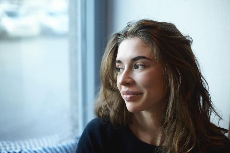Woman looks out window with slight smile